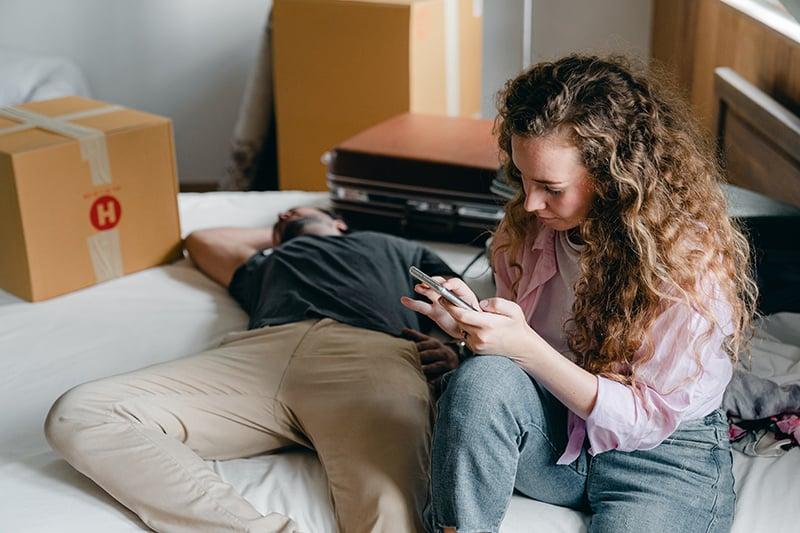 eine Frau, die ein Smartphone in der Nähe eines Mannes benutzt, der auf dem Bett schläft