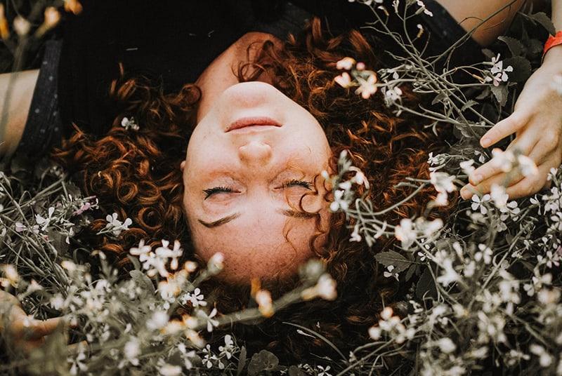 eine Frau mit geschlossenen Augen, die in den weißen Blumen liegt