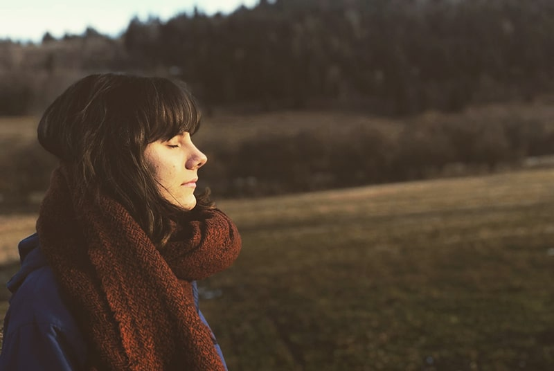 eine Frau mit geschlossenen Augen steht auf dem Feld