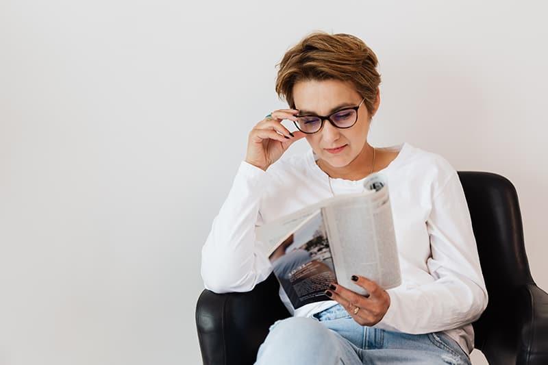 eine Frau mittleren Alters, die eine Zeitung liest, die an sich selbst zweifelt