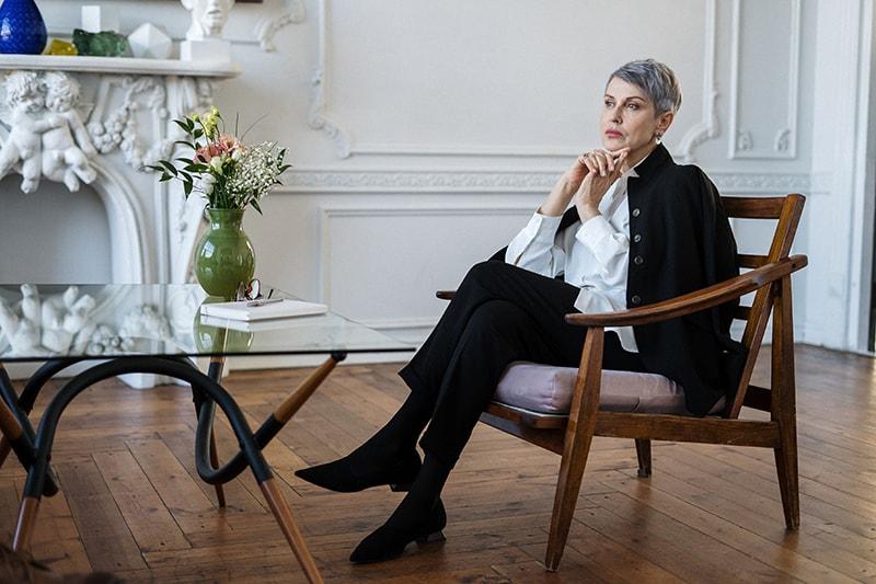Eine Frau mittleren Alters sitzt auf dem Stuhl und denkt nach