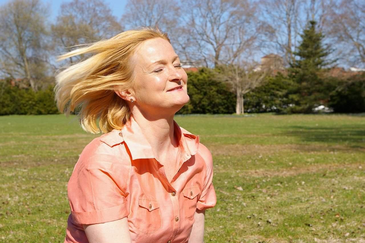eine Frau mittleren Alters mit geschlossenen Augen, die auf dem Rasen im Park steht