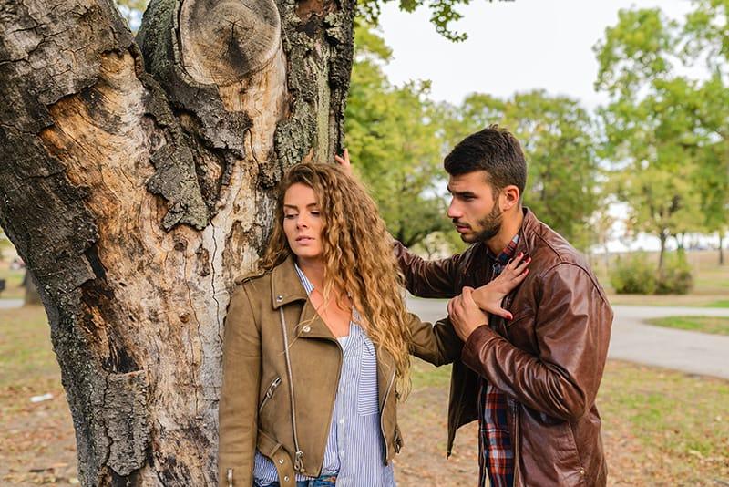 Eine Frau schob einen Mann mit ihrer Handfläche zurück, während ein Mann in der Nähe des Baumes mit ihr sprach
