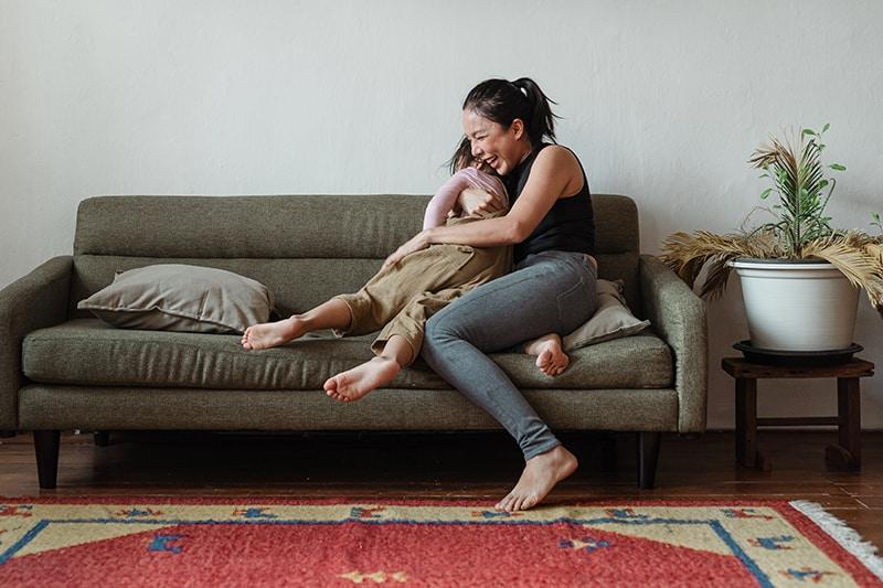eine glückliche Frau, die ihr Kind umarmt, während sie auf der Couch sitzt