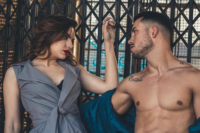 eine Frau und ein Mann, die sich mit Verlangen ansehen, während sie sich auf den Metallzaun stützen