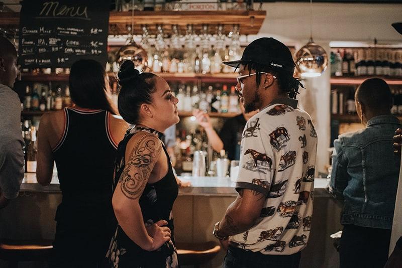 Eine Frau und ein Mann stehen sich gegenüber, während sie in der Bar stehen