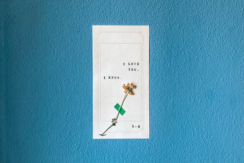 eine Liebesnotiz auf weißem Papier auf blauer Wand