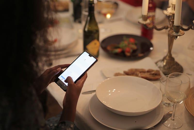 eine Person, die Smartphone während eines Abendessens hält