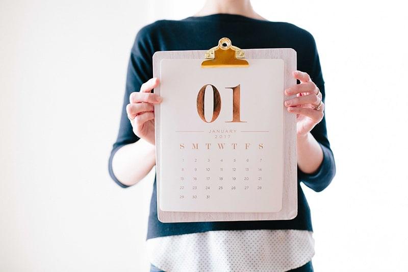eine Person, die im Stehen einen Kalender hält