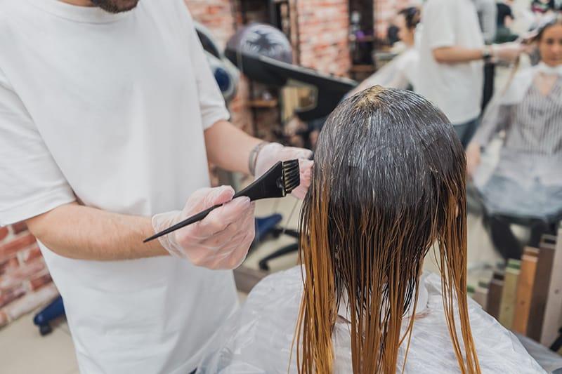 eine Person, die einer Frau in einem Schönheitssalon Haarfärbemittel macht