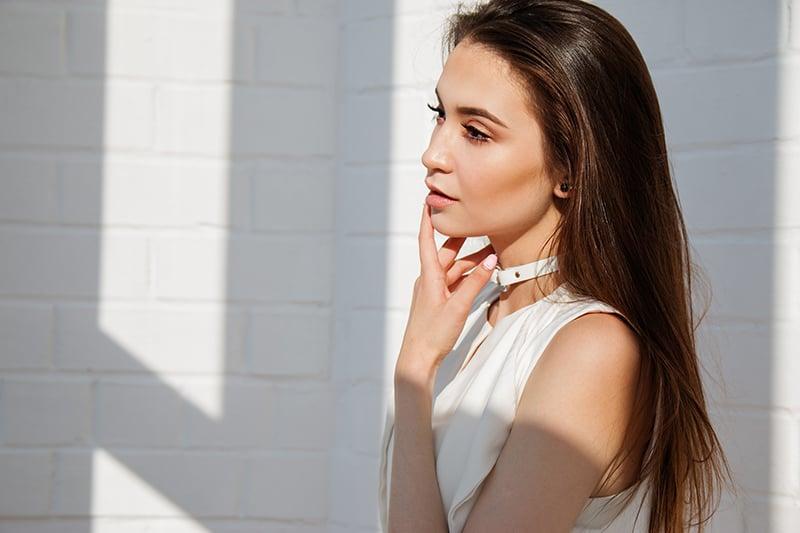 eine attraktive Frau, die Lippen mit der Hand berührt, während sie nahe weißer Wand steht