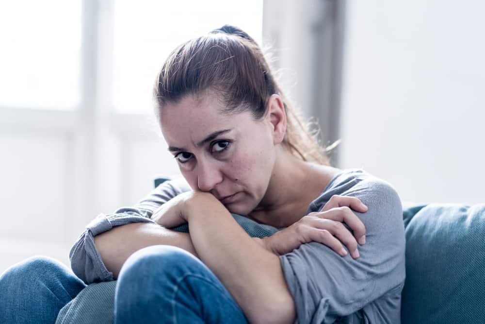 eine attraktive Frau mittleren Alters, die mit einem traurigen Blick sitzt