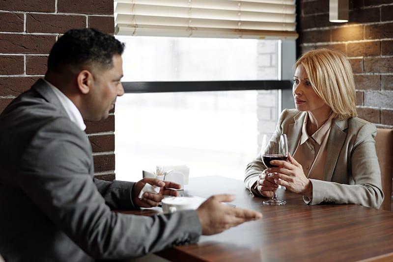 eine besorgte Frau, die einem Mann zuhört, während sie im Restaurant ein Glas Wein hält
