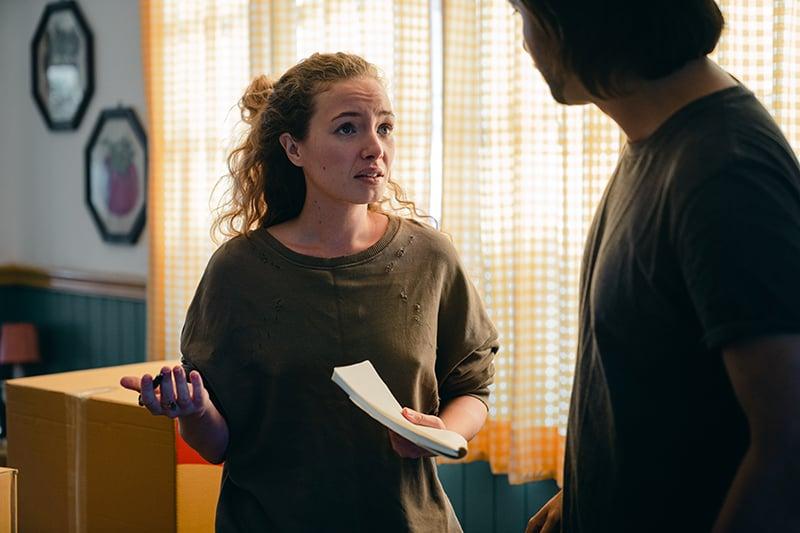 eine besorgte Frau, die mit einem Mann spricht, während sie in einer Wohnung steht