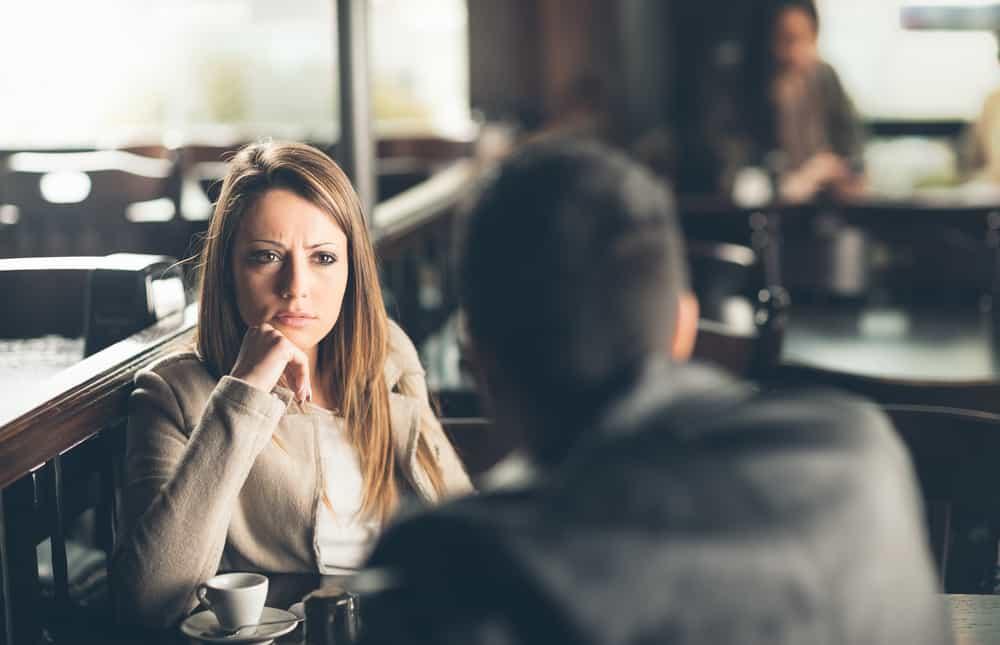 eine besorgte Frau, die mit ihrem Mann in einem Café sitzt