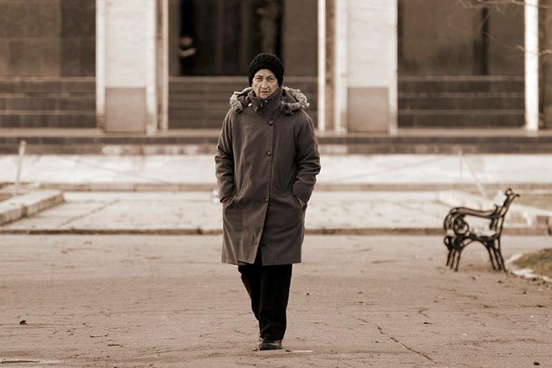 eine einsame ältere Frau, die auf dem Bürgersteig vor dem Gebäude geht