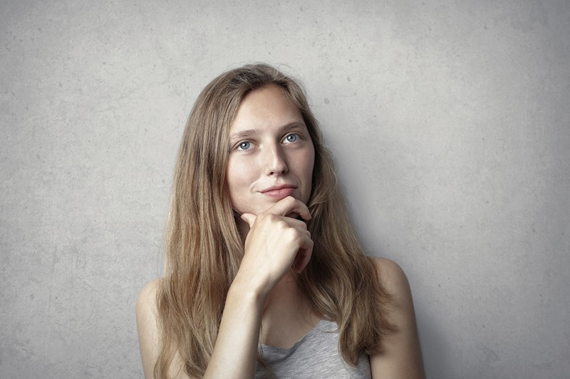 eine entscheidende Frau, die ihr Kinn mit einer Hand berührt, während sie in der Nähe einer grauen Wand steht