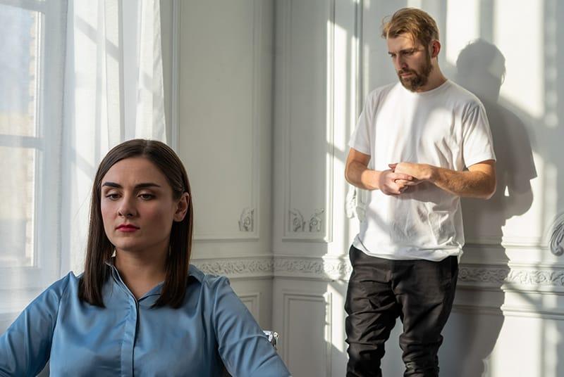 Eine ernsthafte Frau sitzt auf dem Stuhl vor einem Mann, der in der Nähe der Tür steht