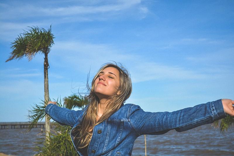 eine freudige Frau, die ihre Arme ausbreitet, während sie in der Nähe des Gewässers steht