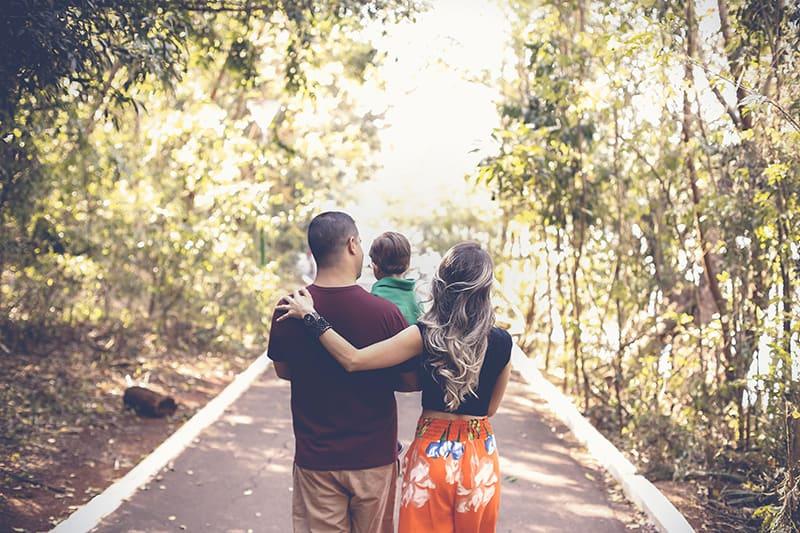 Eine glückliche Familie, die in einem Park spazieren geht, während ein Mann ein Kind trägt und eine Frau ihn umarmt