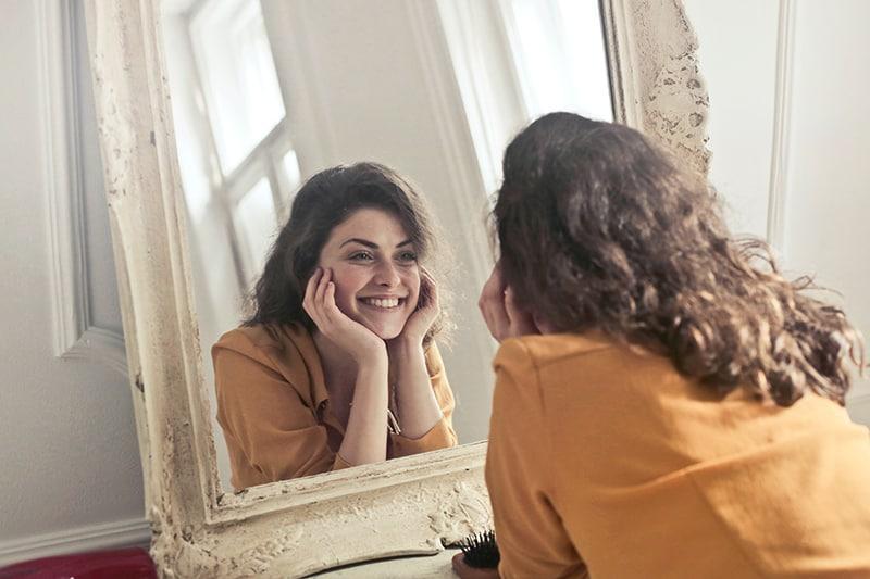 eine glückliche Frau, die sich im Spiegel im Raum ansieht