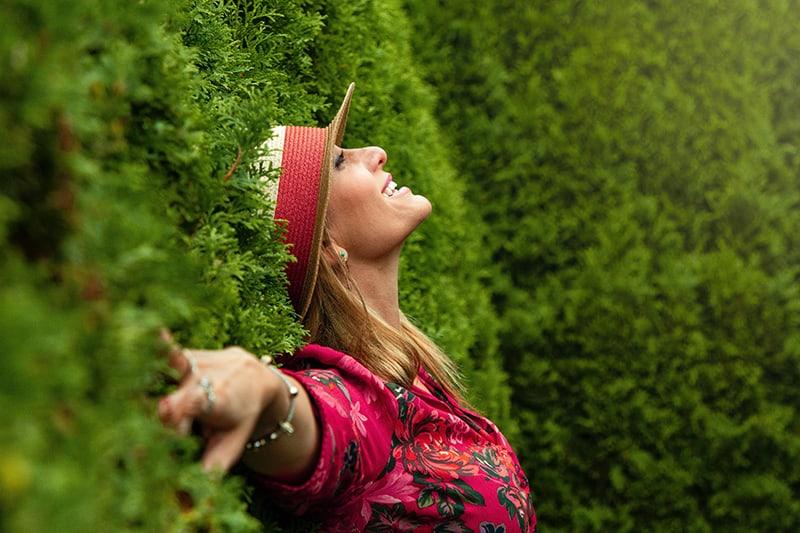 eine glückliche Frau in einem roten Blumenhemd, das sich auf grüne Bäume stützt