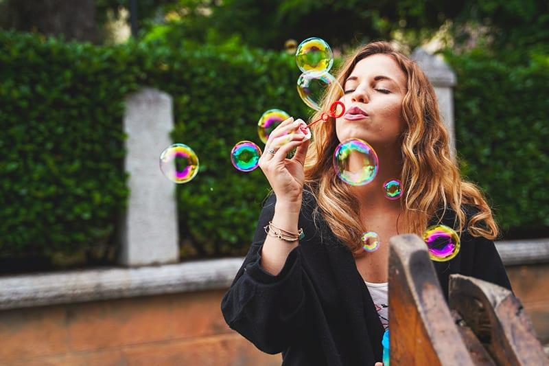 eine kindische Frau, die Blasen macht, während sie draußen steht