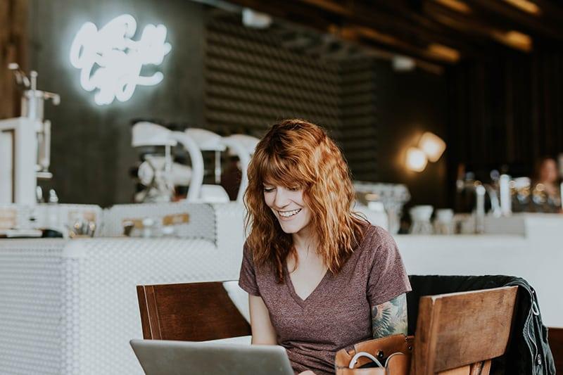 eine lächelnde Frau, die das Internet durchsucht, während sie im Café sitzt