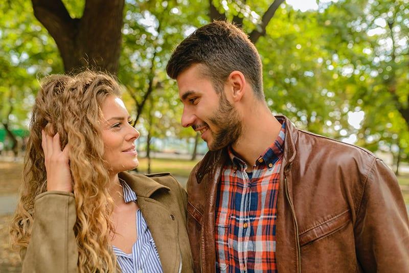 eine lächelnde Frau, die ihre Haare berührt und zu einem Mann schaut, der in ihrer Nähe steht