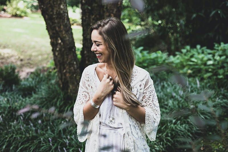 eine lächelnde Frau, die ihre Halskette berührt, während sie in der Nähe von grünen Pflanzen steht