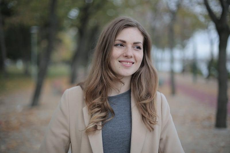 eine lächelnde Frau, die im Park steht, während sie beiseite schaut