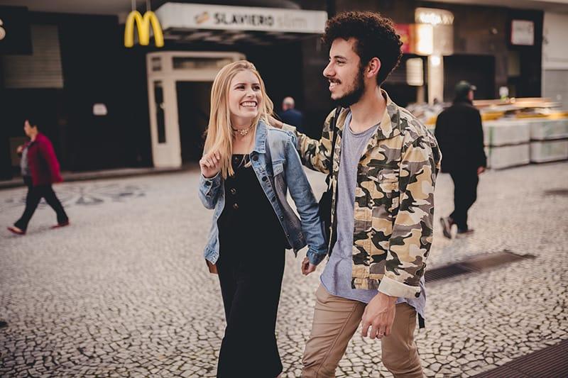eine lächelnde Frau, die mit einem Mann auf dem Bürgersteig geht
