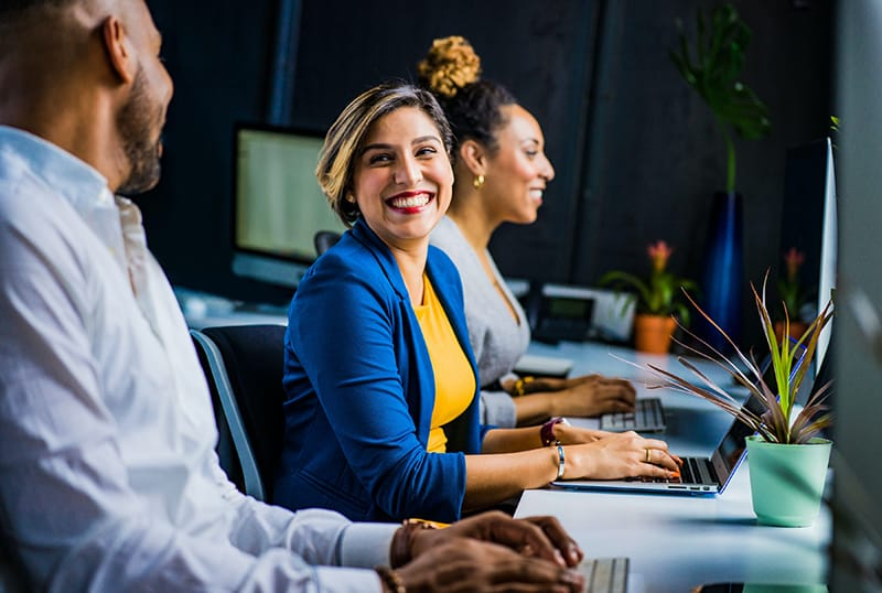 Eine lächelnde Frau, die sich bei der Arbeit mit Kollegen zufrieden fühlt