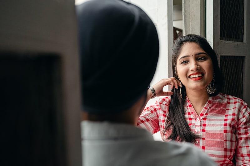 eine lächelnde Frau, die auf einen Mann mit Interesse schaut, während sie in der Nähe des Fensters steht