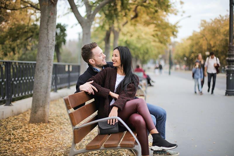 eine lächelnde Frau, die zu einem Mann schaut, während sie zusammen auf der Holzbank sitzt