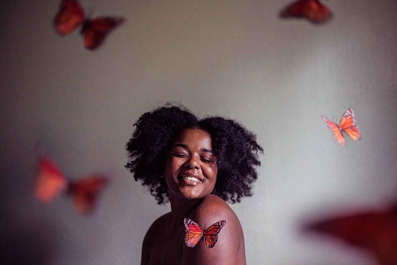 eine lächelnde Frau mit geschlossenen Augen, umgeben von Schmetterlingen