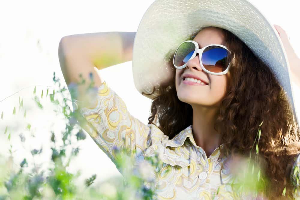 eine lächelnde schöne Frau mit einem Hut und einer Sonnenbrille, die im Gras stehen