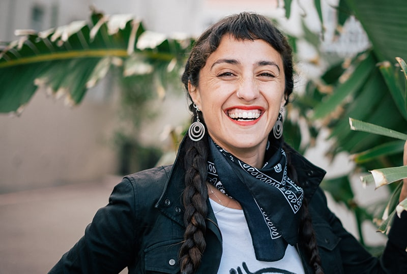 eine lachende Frau, die in der Nähe von grünen Pflanzen steht