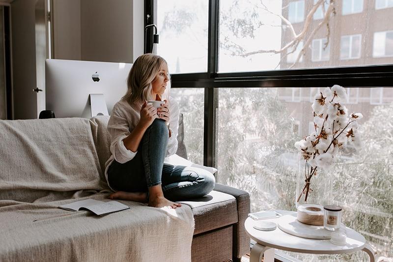 eine nachdenkliche Frau, die am Fenster sitzt und Kaffee trinkt