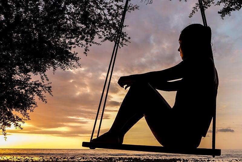 eine nachdenkliche Frau, die auf der Schaukel sitzt und Sonnenuntergang beobachtet