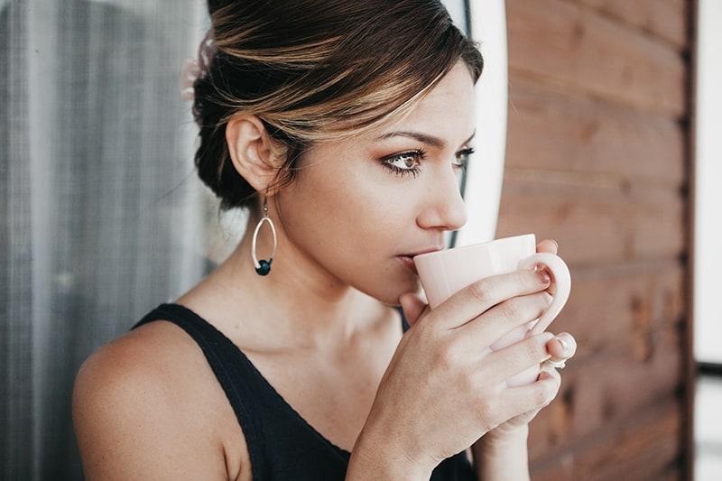 eine nachdenkliche Frau, die einen Kaffee trinkt, während sie draußen steht