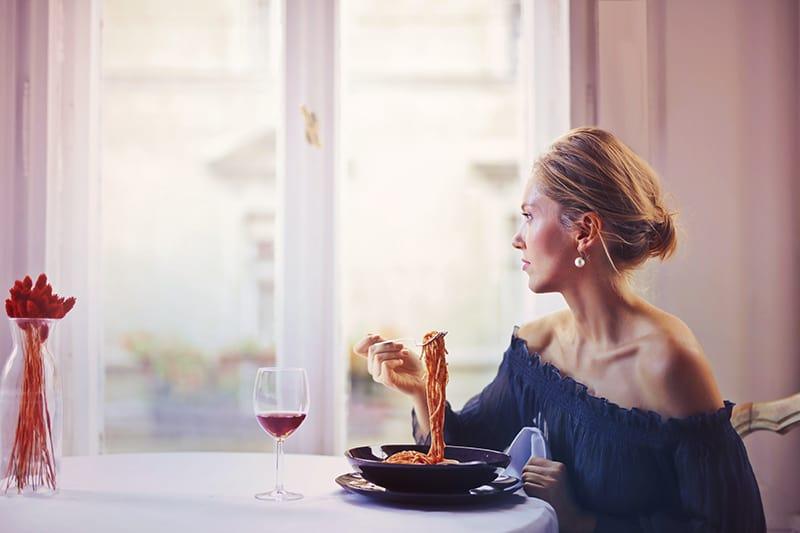 eine nachdenkliche Frau, die gerade Nudeln isst, während sie durch das Fenster schaut