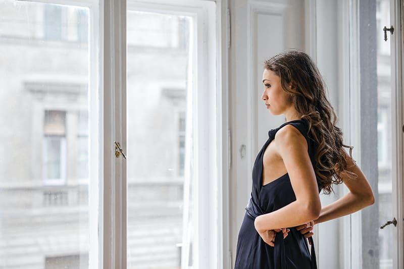 eine nachdenkliche Frau, die neben einem Glasfenster steht, während sie ein Kleid anzieht
