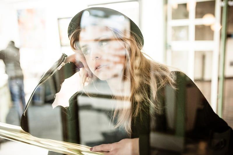 eine nachdenkliche Frau, die sich auf den Handlauf in der Nähe des Glasfensters stützte