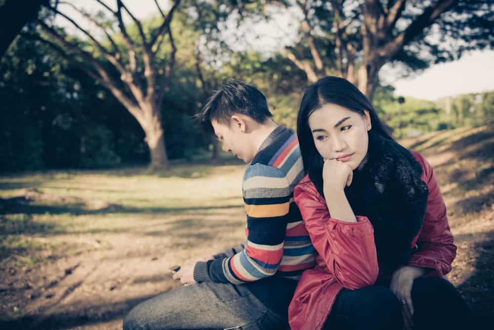 eine nachdenkliche traurige Frau, die mit ihrem Mann auf einer Bank sitzt