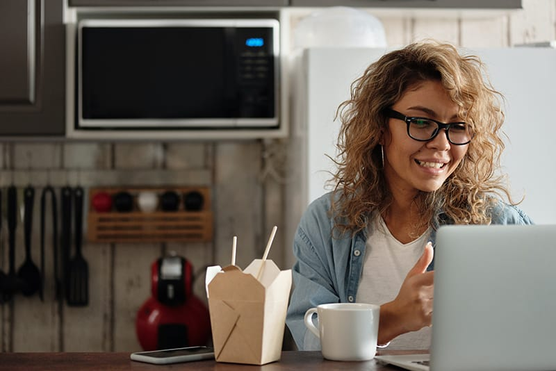 eine positive Frau, die einen Laptop betrachtet, während sie am Tisch sitzt