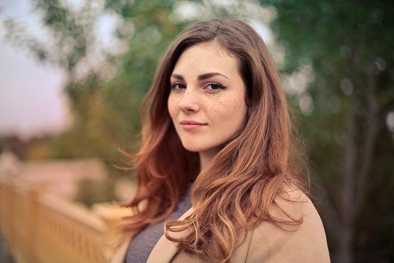 eine schöne Frau in einem braunen Mantel, der nahe dem gelben Handlauf steht