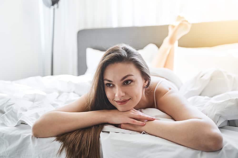 eine schöne junge Frau, die lächelnd auf dem Bett liegt