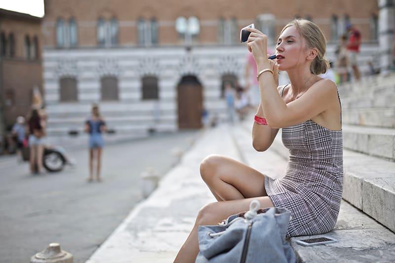 eine schicke Frau, die Lippenstift anwendet, während sie auf Betontreppen sitzt