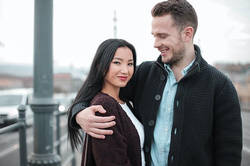 eine selbstbewusste Frau, die in der Nähe eines Mannes steht, der sie umarmt